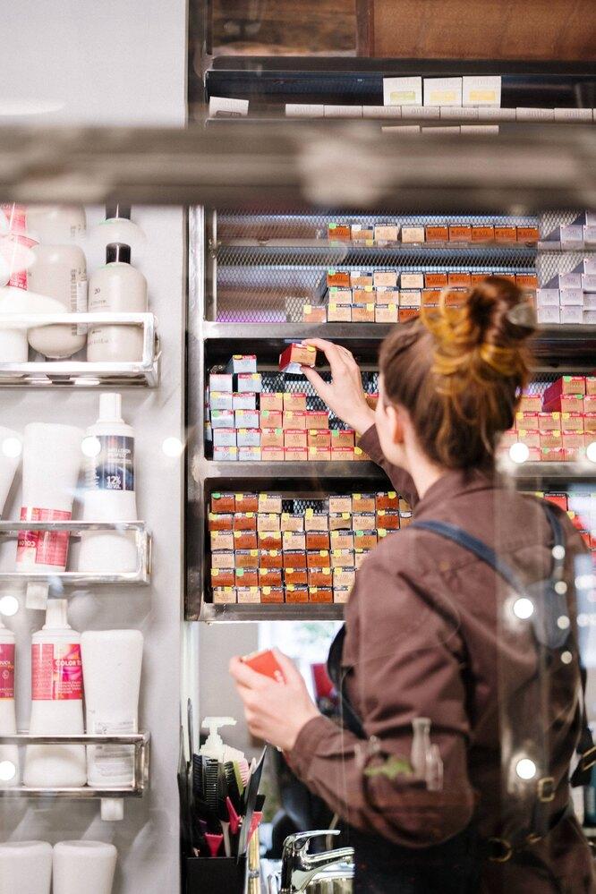 краска в магазине, выбор красителя в магазине, девушка выбирает краску